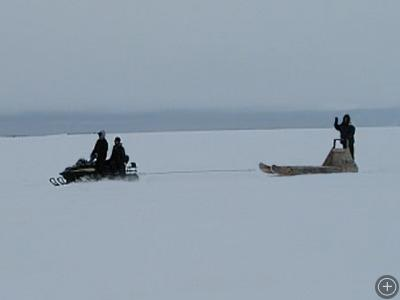 Snowmobiles versus dog sleds. Photo by Chico Perales